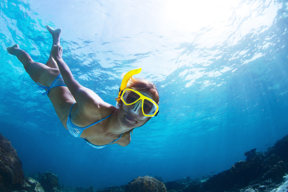 a picture of a girl snorkleing at baby beach aruba