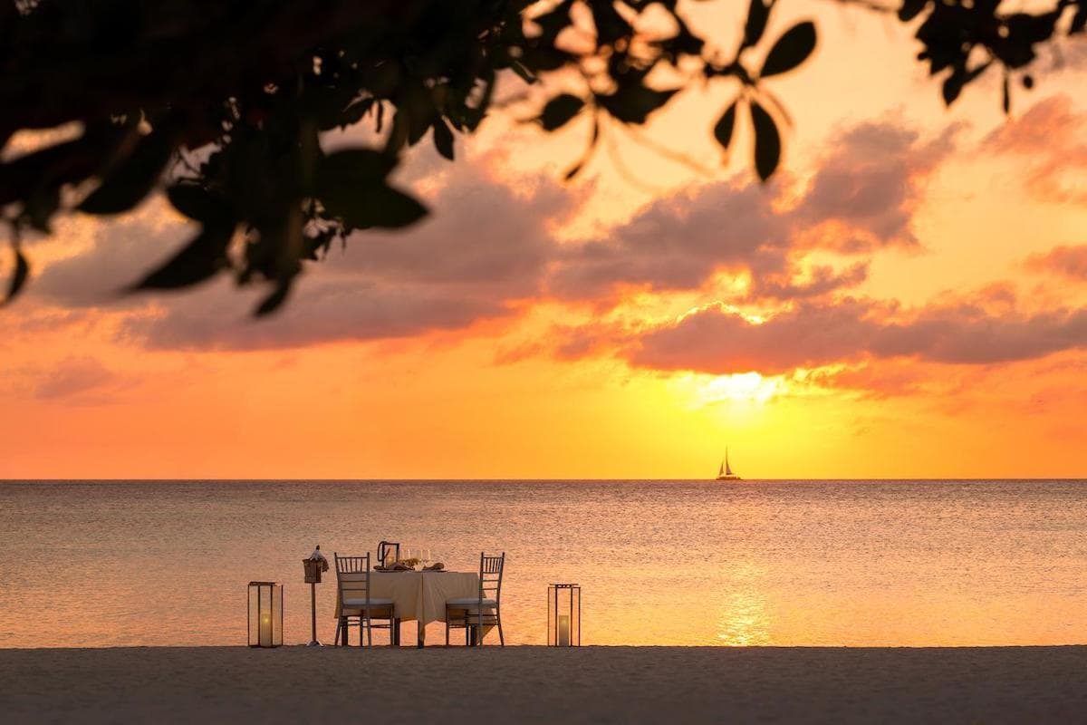 a dining table set up on Palm Beach in Aruba
